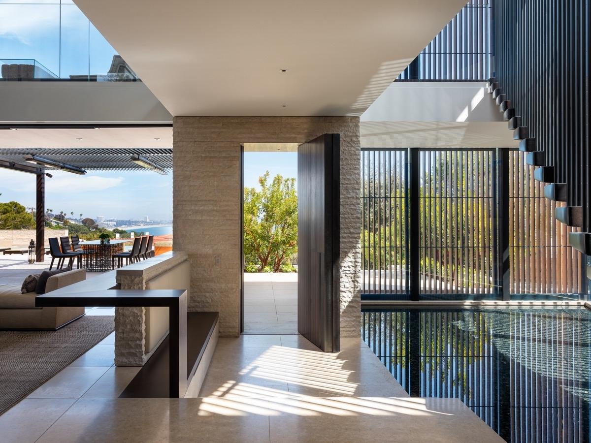 Biệt thự có cả bể bơi trong nhà, phản chiếu bóng cầu thang và cửa chớp phía trước.