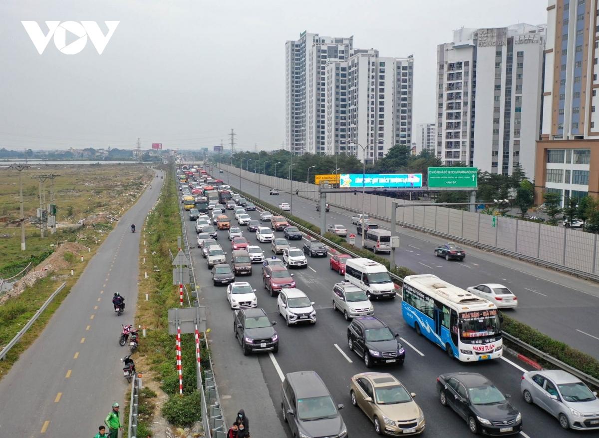 Dòng phương tiện ùn ứ, nhích từng cm trên cao tốc. Nhiều người đi xe khách đã chọn phương án xuống xe giữa đường, trèo qua dải phân cách để vào đường gom bắt xe ôm và taxi.