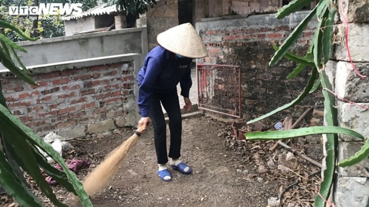 Bà Chính lấy chổi quét vườn cho nhà bà H.