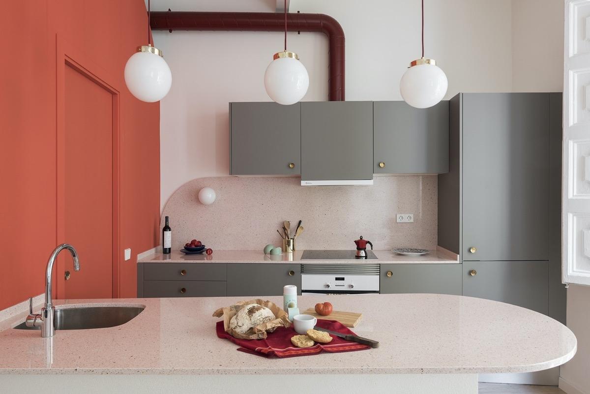 Màu xám của tủ bếp làm dịu mắt mảng tường màu nóng ở bên cạnh.