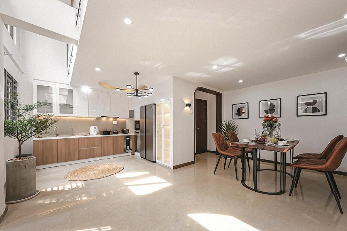 Đây là một ngôi nhà phố nằm ở quận Phú Nhuận, TP Hồ Chí Minh. Diện tích xây dựng khá khiêm tốn, chưa tới 40m2. Vì thế cấu trúc công trình được phát triển theo chiều cao với mỗi tầng là một chức năng chủ đạo riêng biệt. Ở tầng 1 là phòng bếp – ăn. Không gian này được thiết kế mở và kết nối với khoảng thông tầng phía trên nên luôn thoáng sáng.
