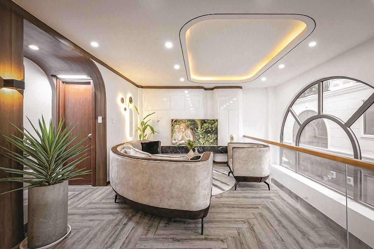 Vị trí đặt sofa kế bên khoảng thông tầng với ô cửa vòm lớn. Lan can kính góp phần mở rộng không gian và tăng cường chiếu sáng.