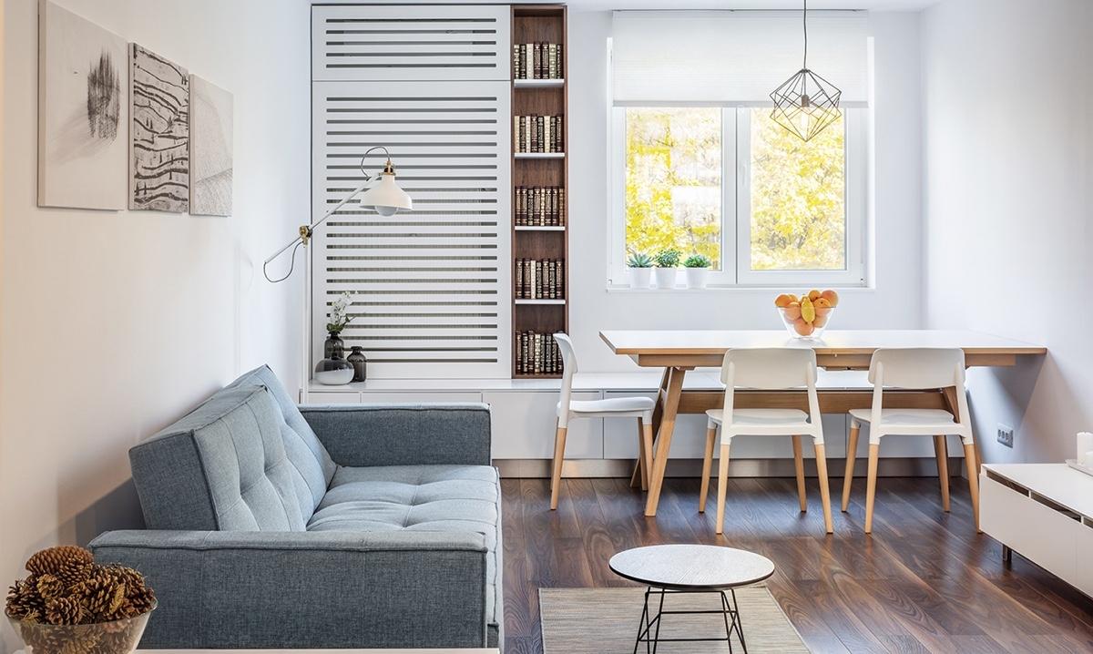 Căn hộ studio 1 phòng ngủ nhỏ gọn này tạo cảm giác nhẹ nhàng, thoáng mát khi sử dụng màu sơn trắng và đồ nội thất sáng màu. Bàn được đặt dọc theo cửa sổ với đèn thả để cung cấp nhiều ánh sáng.