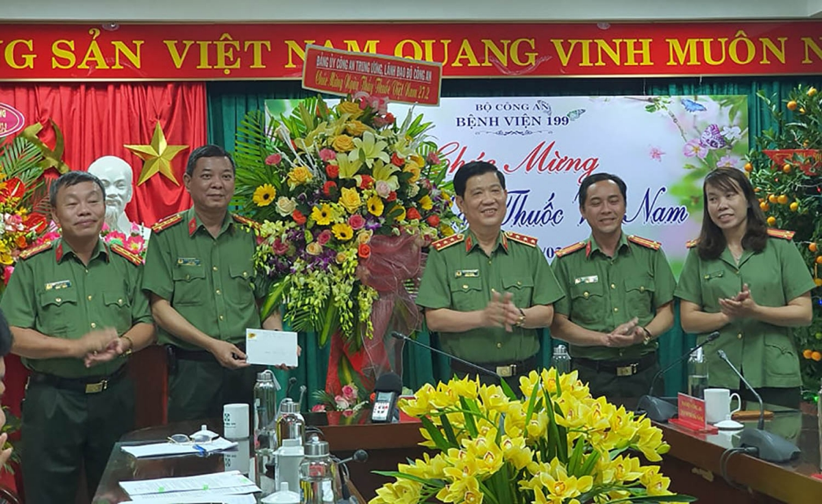 Thứ trưởng Nguyễn Văn Sơn (đứng giữa bên phải) tặng hoa cho cán bộ Bệnh viện 199.
