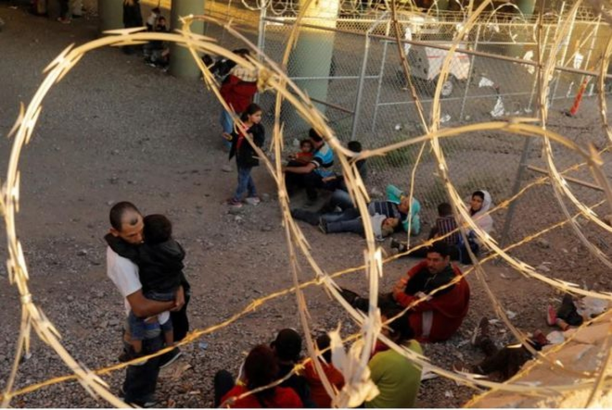Người di cư từ các quốc gia Trung Mỹ bị tạm giữ tại thành phố El Paso (bang Texas) sau khi vượt biên để xin tị nạn ở Mỹ (Ảnh: Reuters)