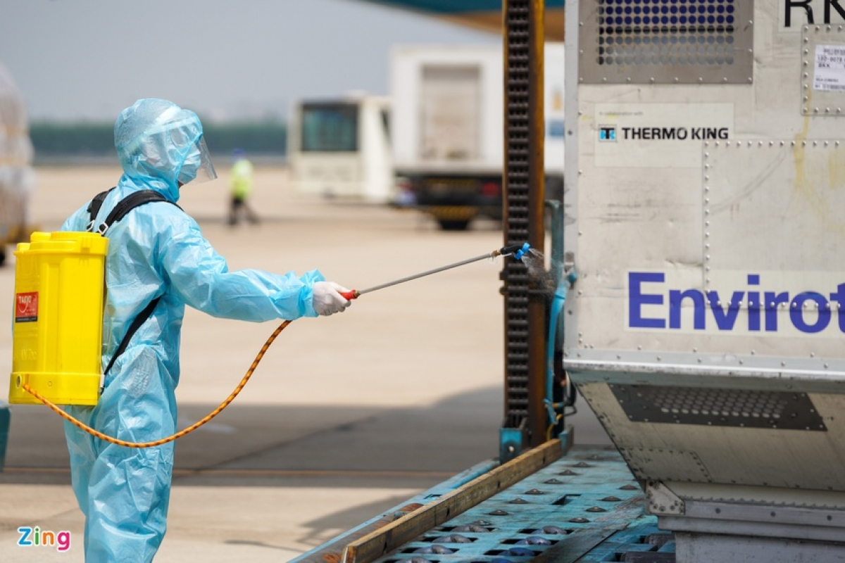 As part of regulations on all imported items, medical workers thoroughly spray disinfectant over the shipment.