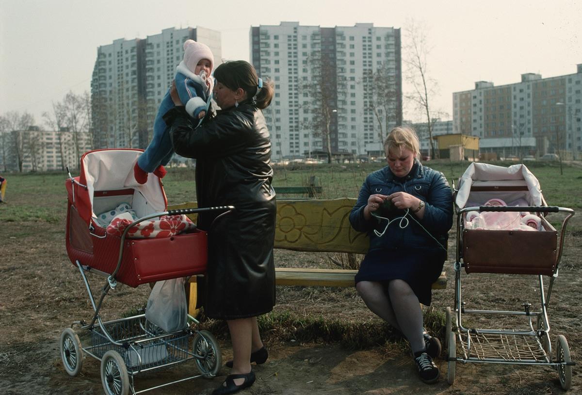 Các bà mẹ bỉm sữa và con mình trong xe nôi. Phía xa xa có lẽ là các chung cư.