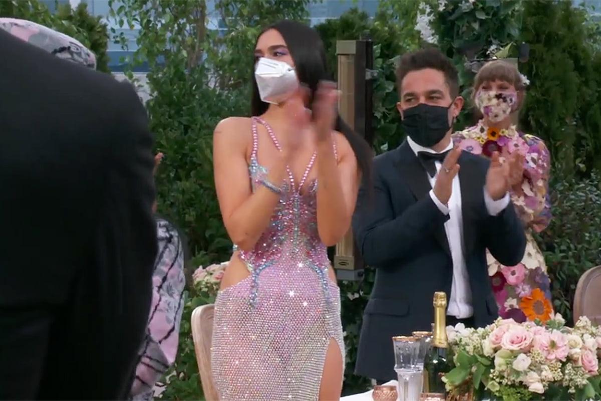 Nữ ca sĩ Dua Lipa chọn khẩu trang màu bạc lấp lánh khi diện thiết kế đầm xẻ bạo của Versace.