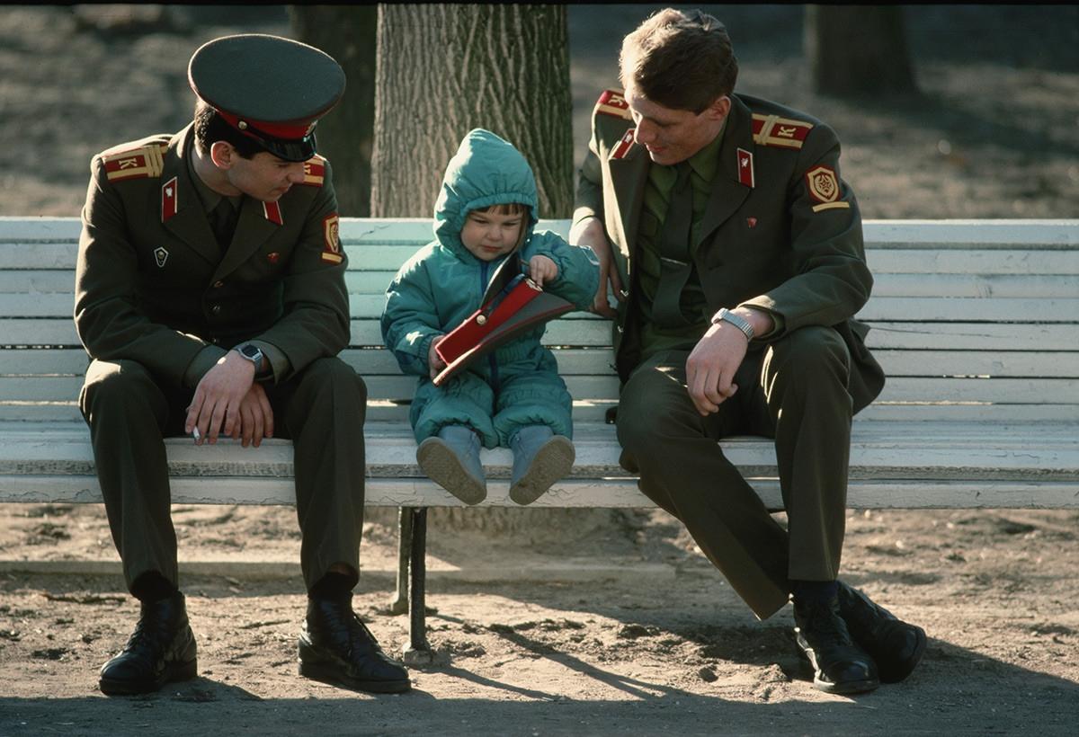 Binh sĩ Liên Xô ngồi trên ghế băng cùng 1 em bé.