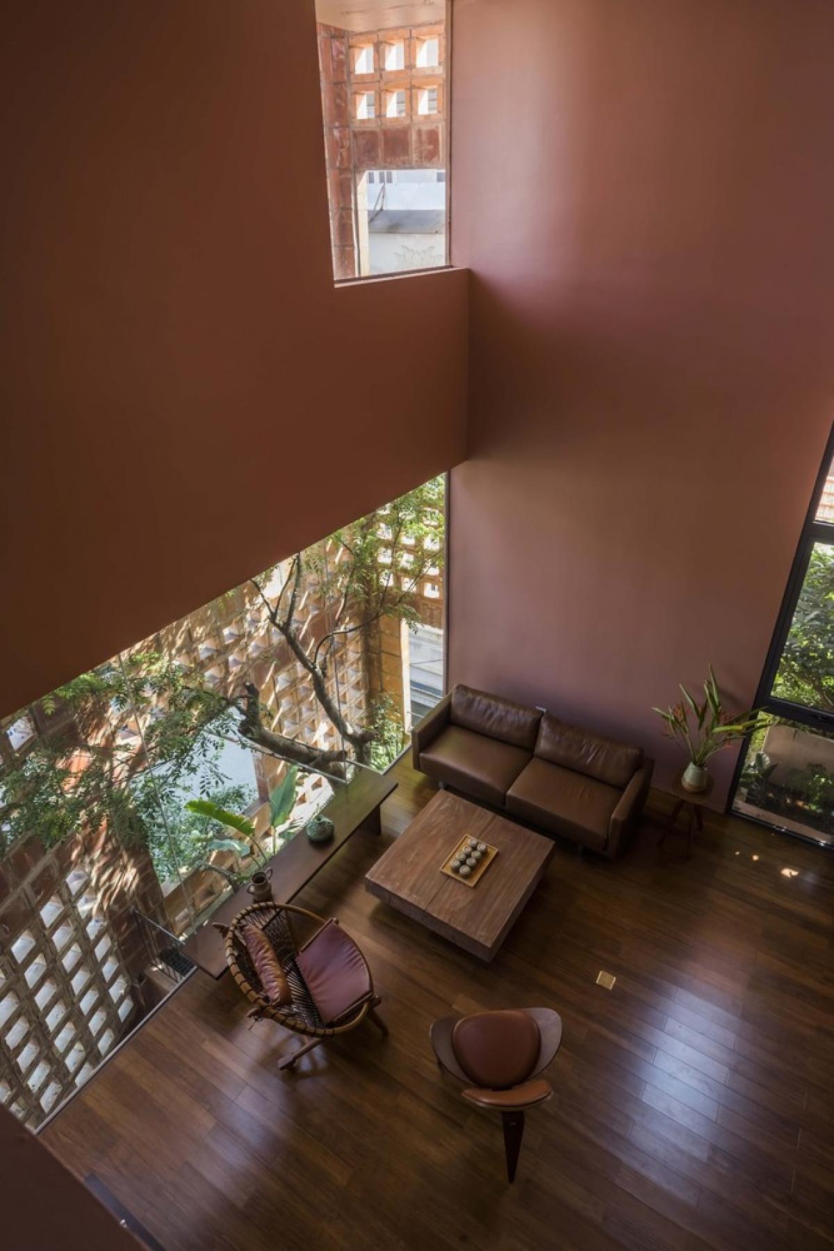 Đằng sau lớp gạch gốm là hệ cây xanh với những cây thân cao vươn tán lá rợp qua những ô cửa sổ lớn.