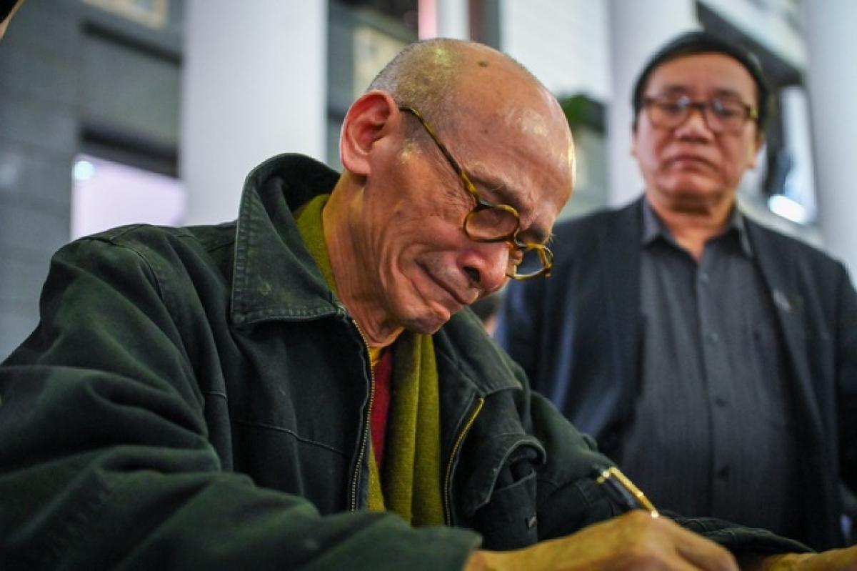 Nhà văn Nguyễn Văn Thọ xúc động ghi sổ tang.