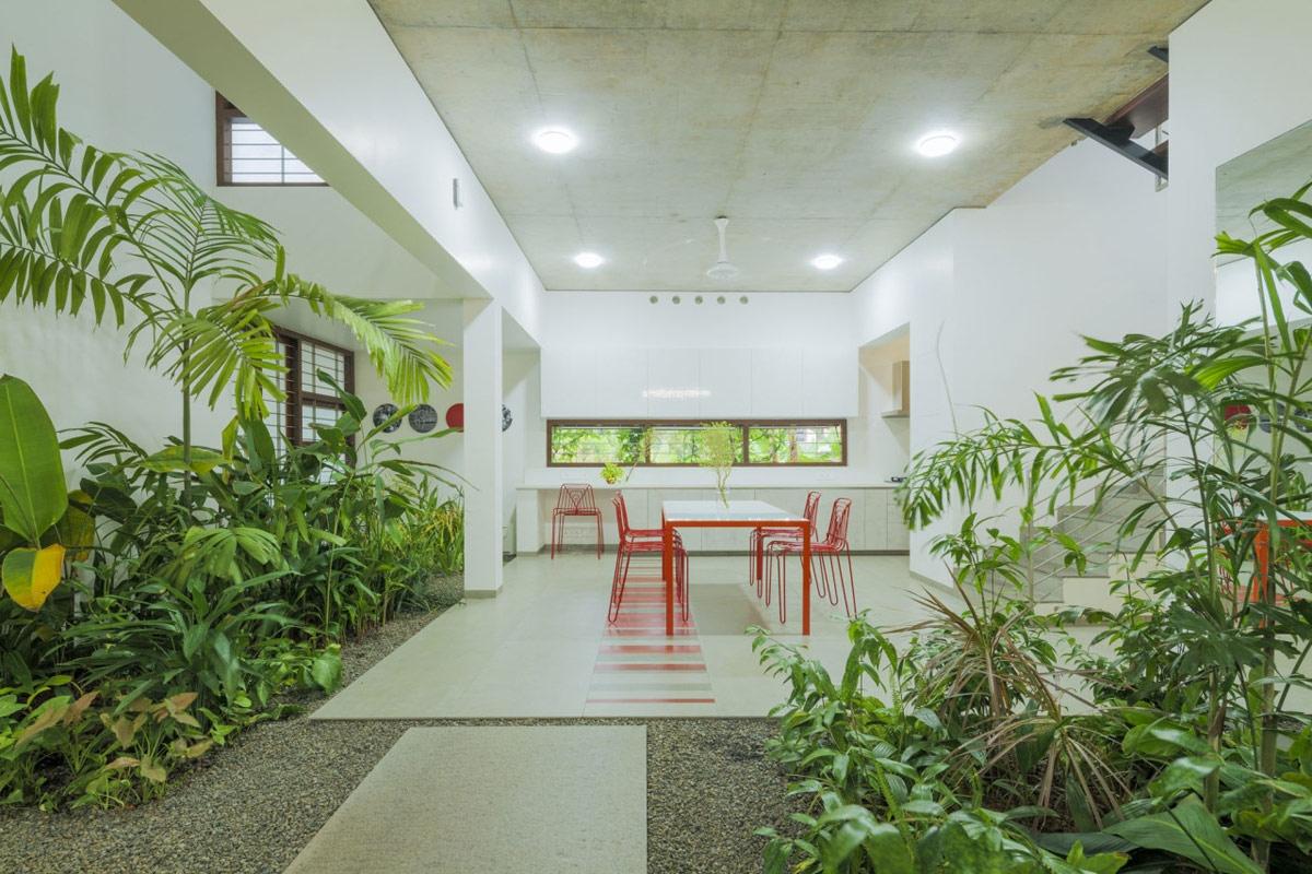 Đằng sau bộ bàn ăn là căn bếp hiện đại, với bức tường trải dài với cửa sổ, mở ra mặt sau của khu vườn.
