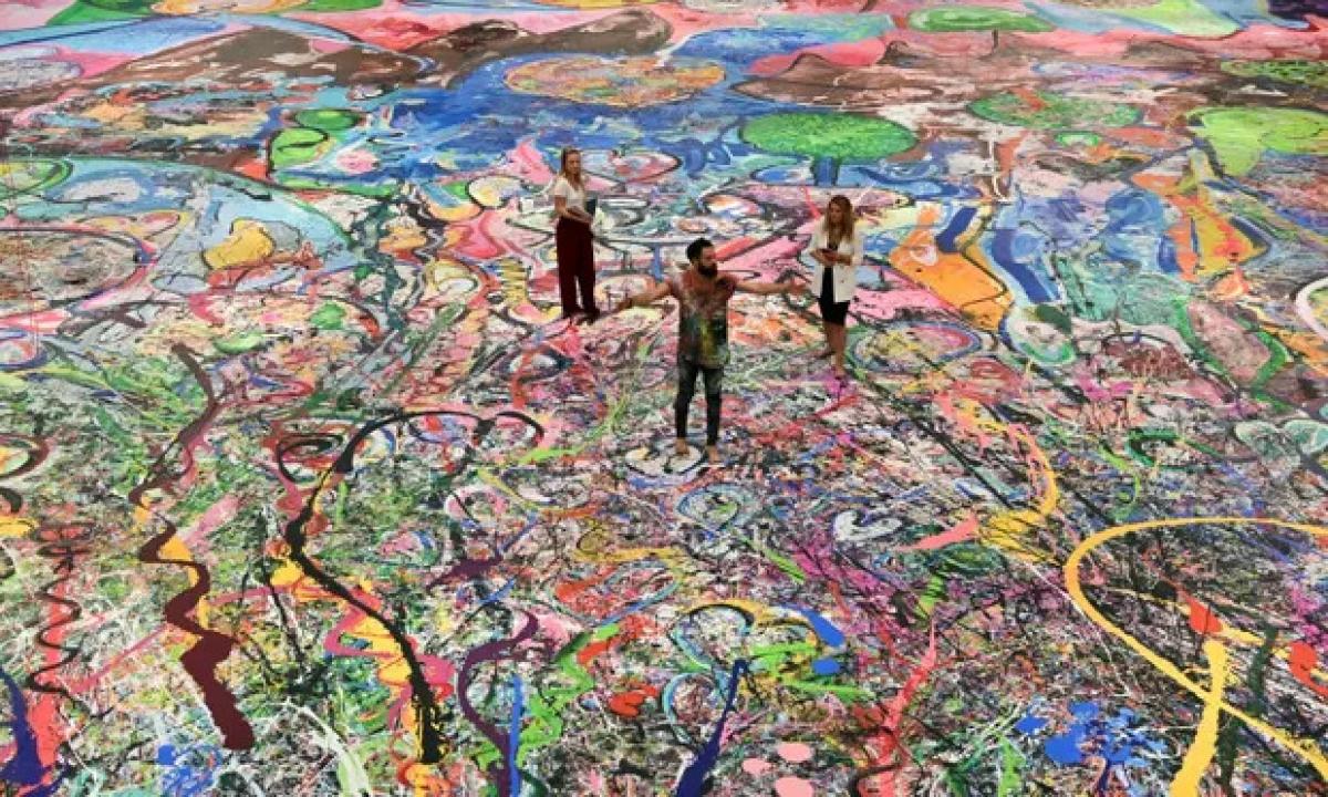 Họa sĩ người Anh Sacha Jafri (giữa) đứng trên tác phẩm đạt kỷ lục guinness của mình ở thành phố Emirati, Dubai.