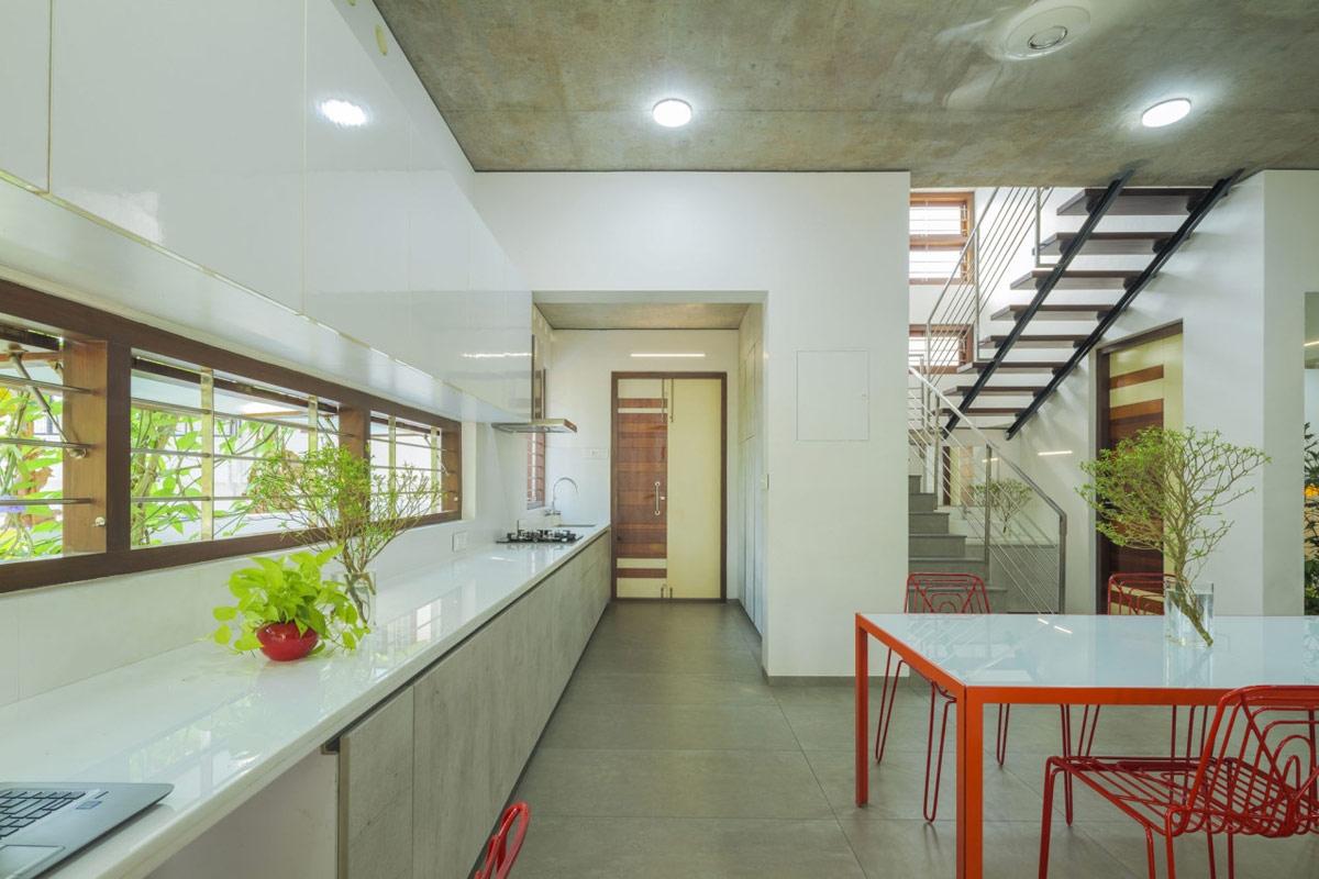 Căn bếp nhận được ánh sáng và không gian xanh từ dãy cửa sổ.