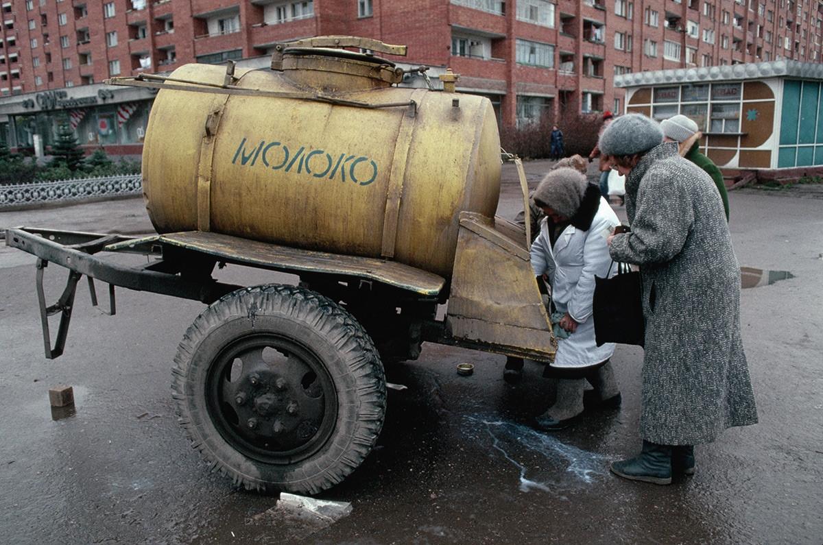 Phụ nữ mua sữa đựng trong téc trên một xe 2 bánh.