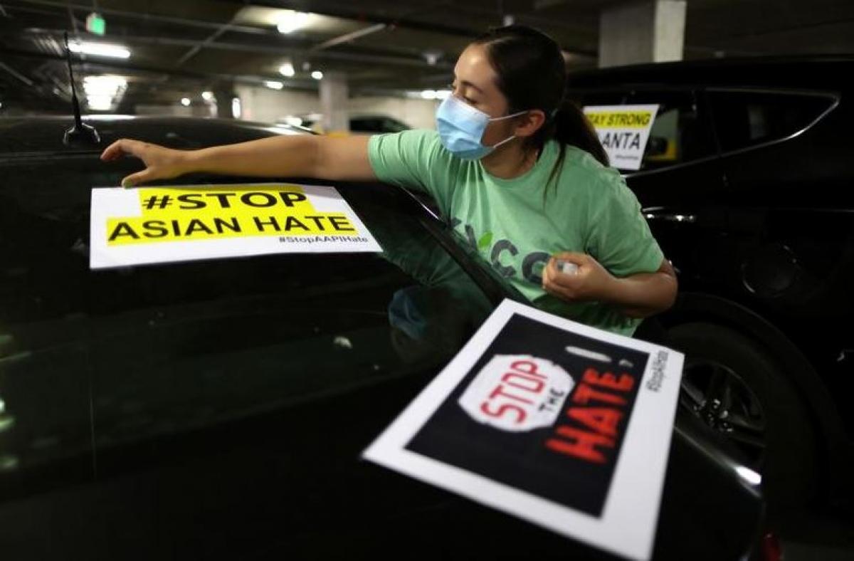 Aida Martinez dán những tấm poster lên ô tô của cô trong cuộc biểu tình phản đối sự thù ghét nhằm vào những người Mỹ gốc Á sau vụ xả súng ở cửa hàng Young's Asian Massage ngày 19/3. Ảnh: Reuters