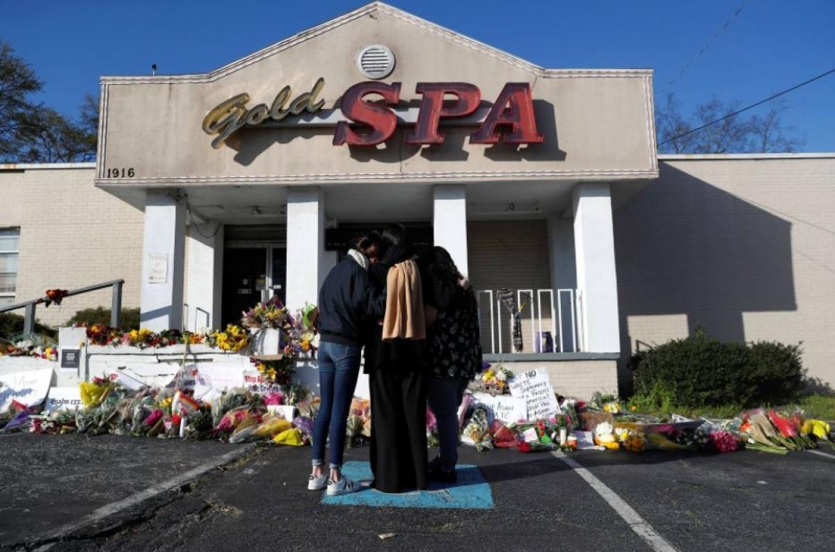 Một vài người ôm nhau tại một địa điểm tưởng niệm tạm thời trước cửa hàng Gold Spa ở Atlanta ngày 20/3. Ảnh: Reuters