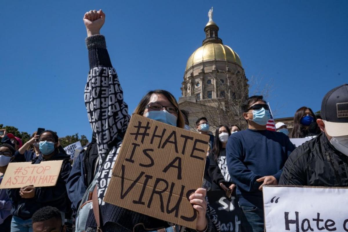 """Những người biểu tình giơ cao những tấm bảng với các thông điệp như: """"Hãy chấm dứt sự thù ghét với người gốc Á"""" hay """"Sự thù ghét mới là virus"""". Ảnh: Getty"""