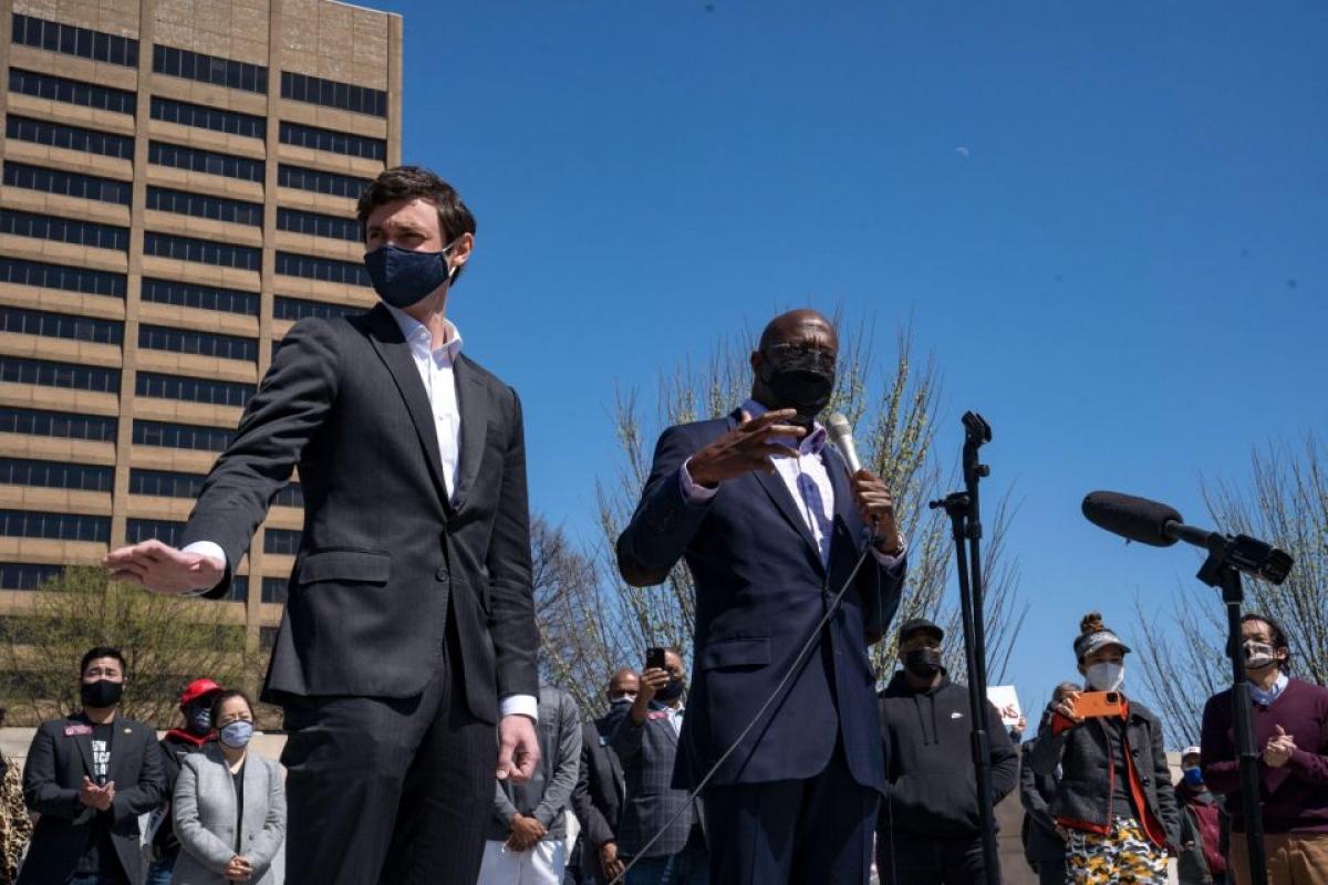 """Các thượng nghị sĩ bang Georgia Jon Ossoff (trái) và Raphael Warnock phát biểu trước những người biểu tình ở Atlanta ngày 20/3. Ông Warnock khẳng định: """"Hỡi những người anh chị em châu Á của tôi, tôi muốn nói với các bạn rằng chúng tôi sẽ luôn dõi theo các bạn và quan trọng hơn, chúng tôi sẽ đứng về phía các bạn"""". Ảnh: Getty"""