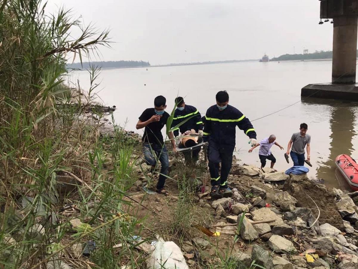 Lực lượng chức năng đưa thi thể lên bờ.