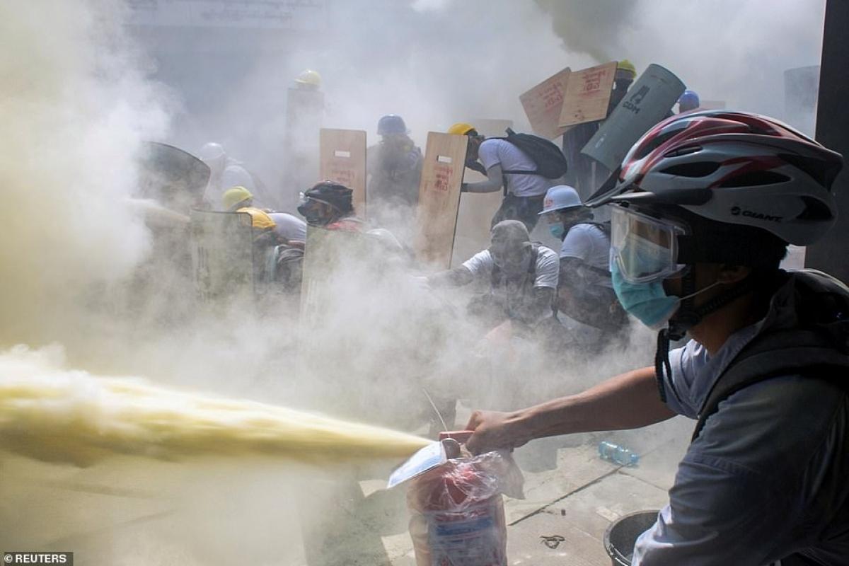 Một người biểu tình dùng bình cứu hỏa xịt về phía cảnh sát để chống trả.
