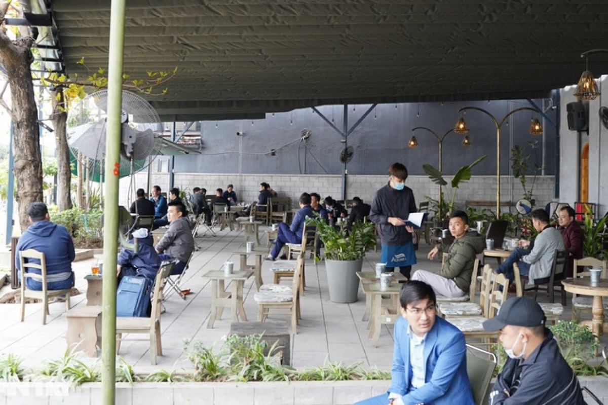 A coffee shop situated on Le Duc Tho street is full of customers at 11:00 a.m.