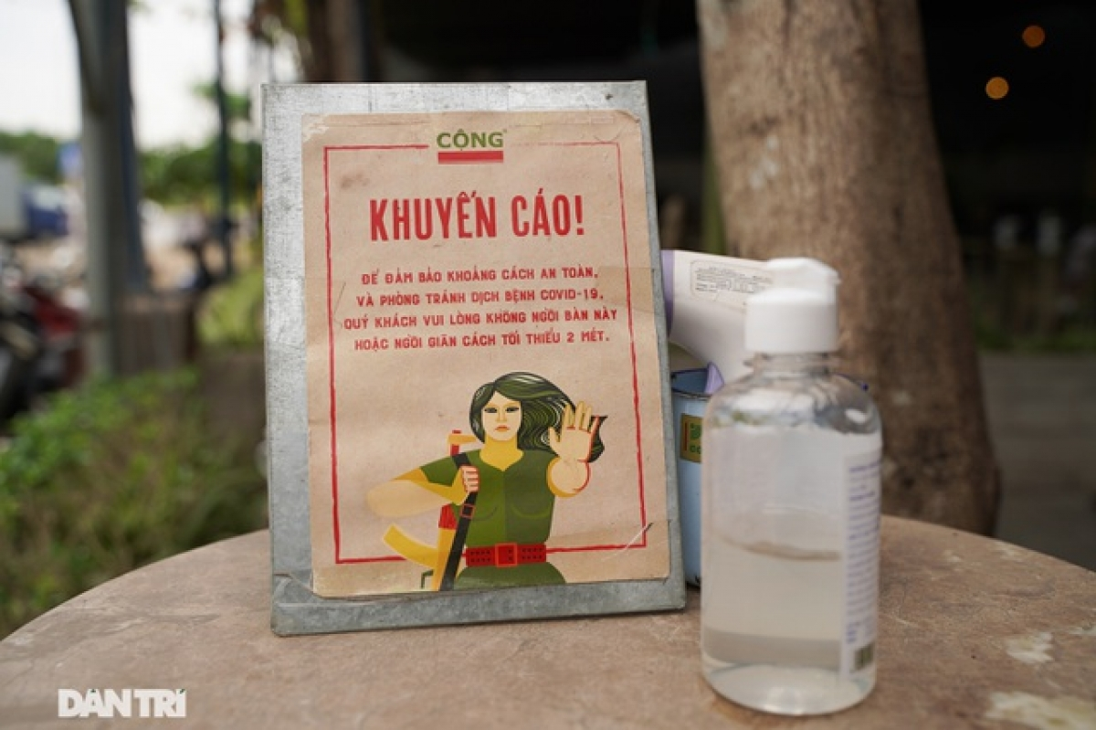 A notice detailing COVID-19 prevention measures is placed alongside a bottle of hand sanitizer on a table in front of a coffee shop.
