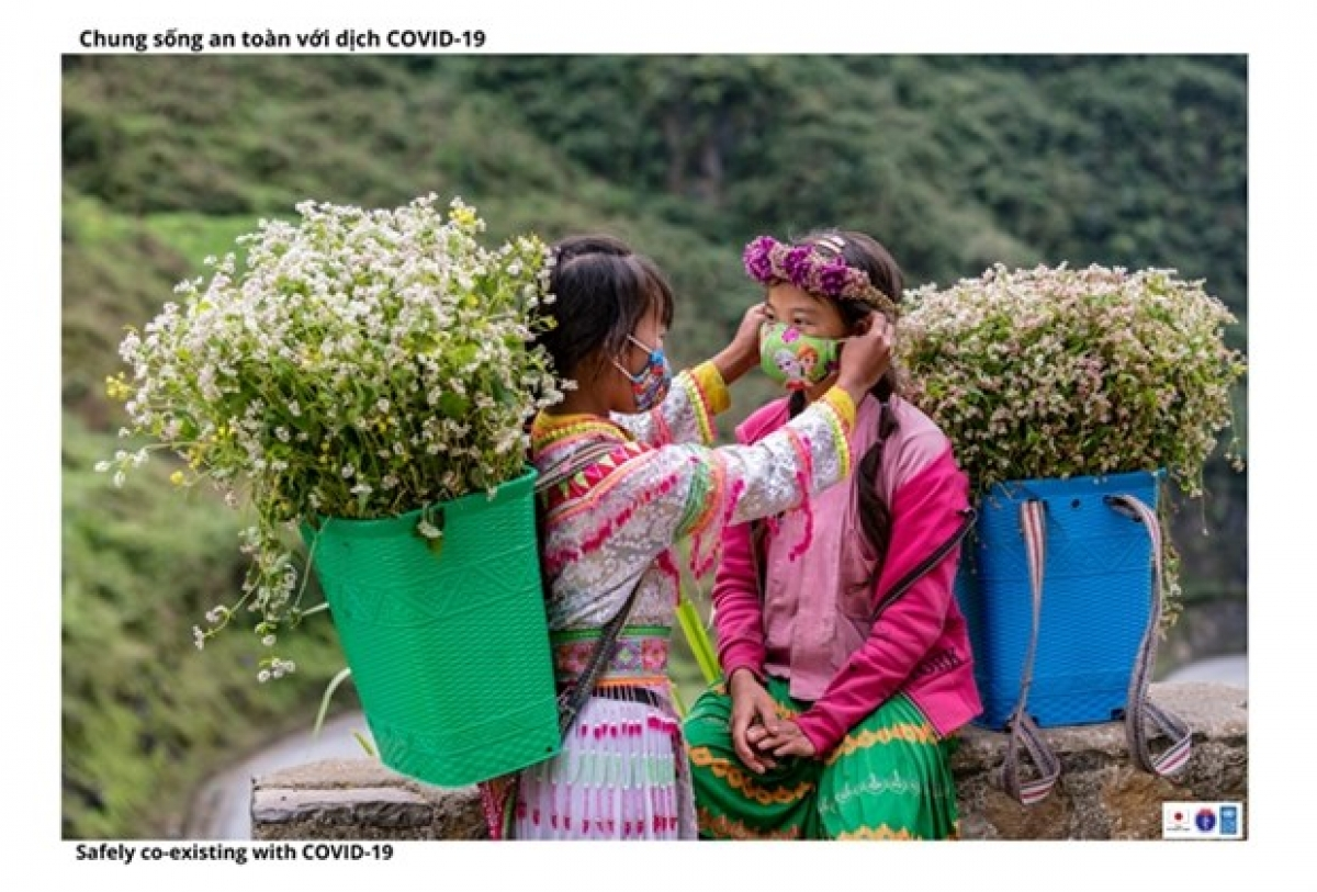 Two ethnic minority girls wear masks while selling flowers to tourists at Tham Ma slope, northern mountain Hà Giang province. (Photo courtesy of the MoH)