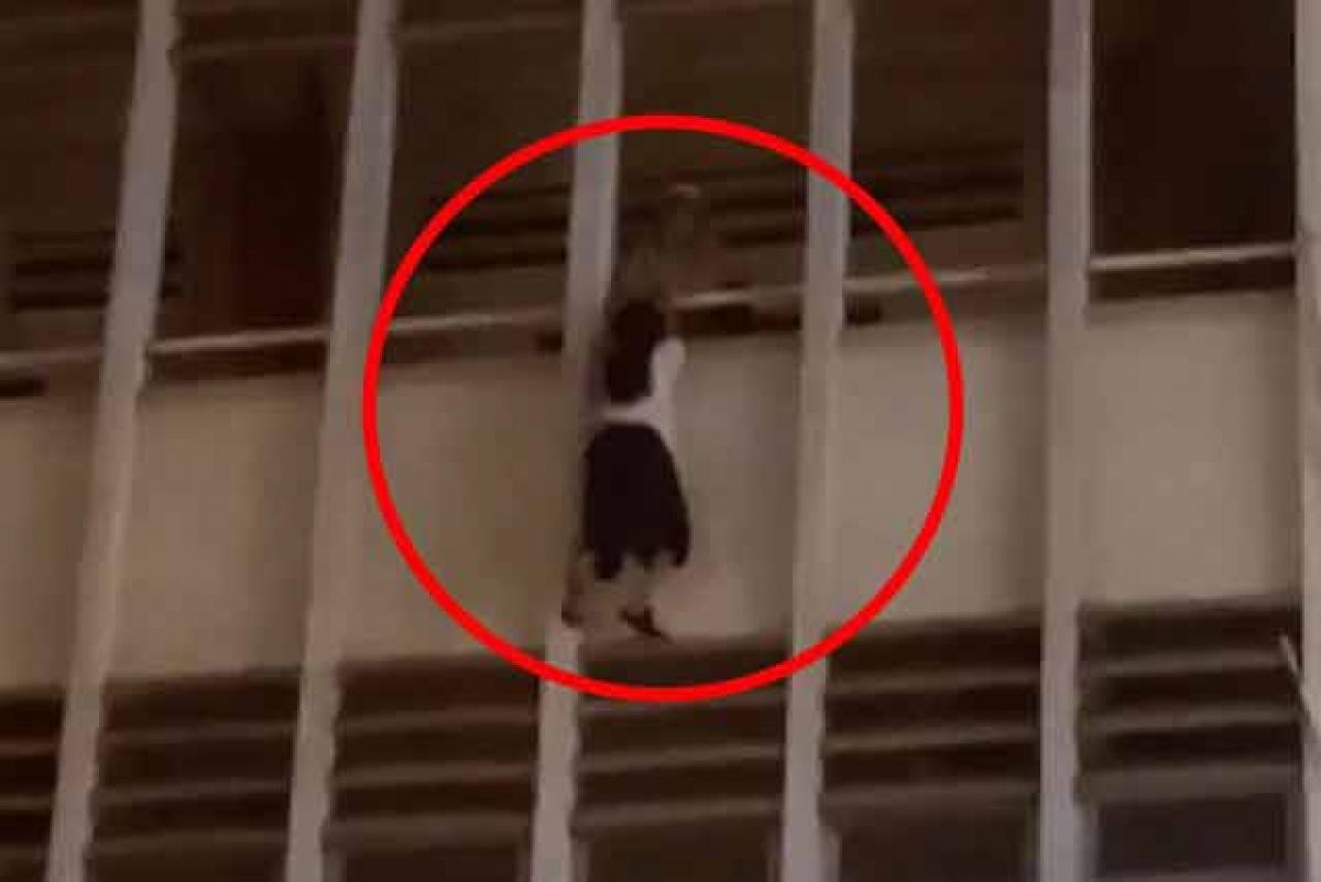 Nữ sinh được người đàn ông cứu khi đang lơ lửng bên ngoài lan cang ở tầng 3. Ảnh cắt từ clip