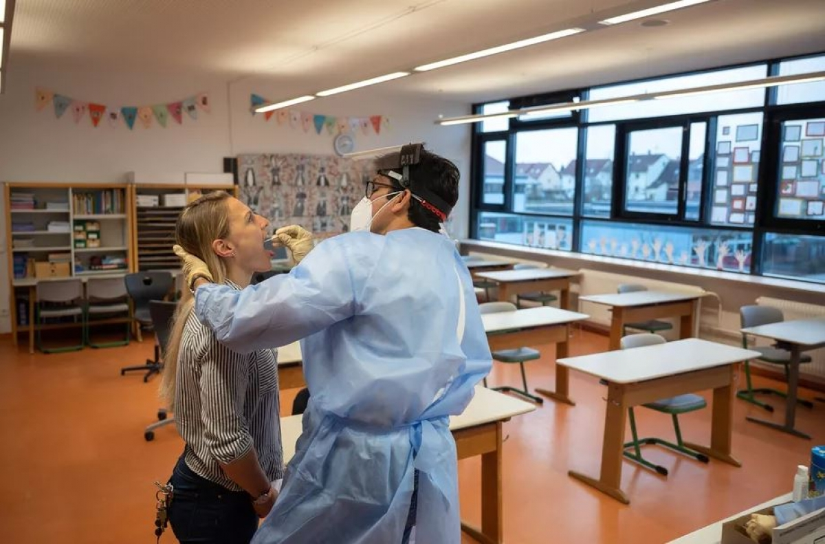 Ảnh minh họa: Một bác sĩ tiến hành lấy mẫu xét nghiệm cho một giáo viên. Ảnh: Getty