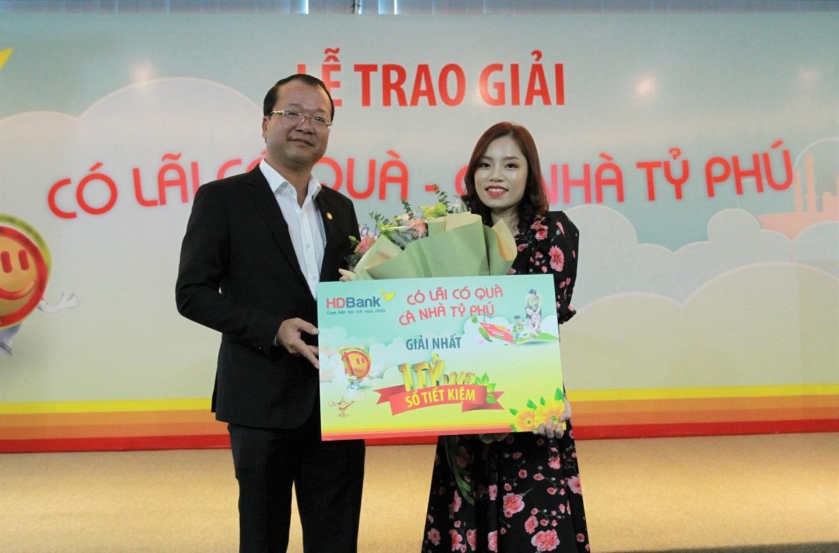 Ông Trần Quốc Anh - giám đốc khối KHCN HDBank chúc mừng khách hàng Đinh Thị Tuyết Nhung đã may mắn trúng giải nhất chương trình ưu đãi hè 2020.