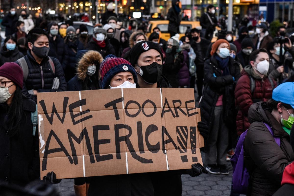 """Một phụ nữ cầm biểu ngữ ghi thông điệp """"Chúng tôi cũng là người Mỹ"""" như thể hiện sự chua chát của những người gốc Á khi bị phân biệt đối xử ở Mỹ. Ảnh: AFP"""