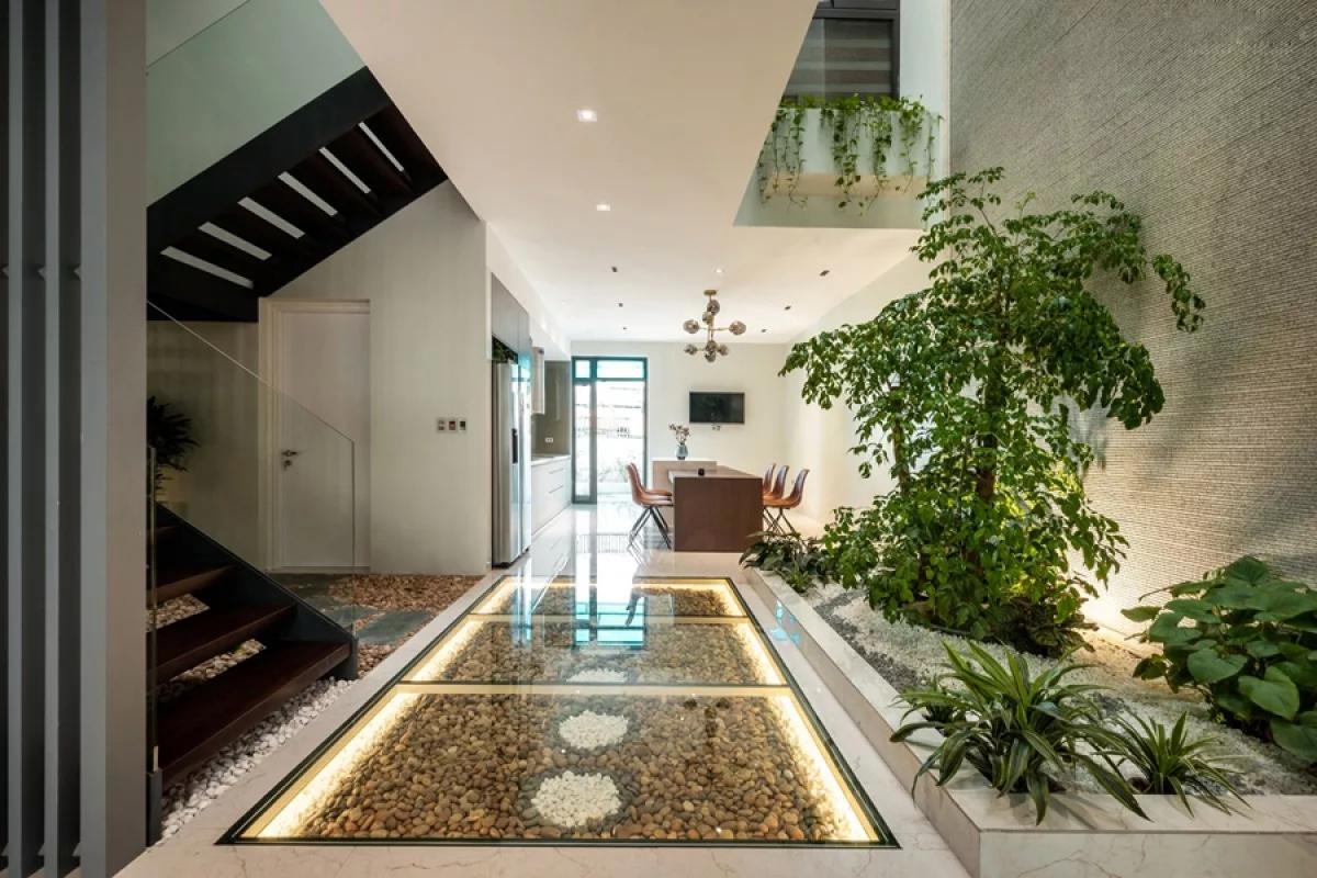 Điểm nhấn trong nhà là khu vực giữa rộng gần 20m2, bao gồm hệ cầu thang nối từ tầng một lên tầng ba, khoảng thông kế bên cầu thang thông suốt từ mái xuống tầng 1.