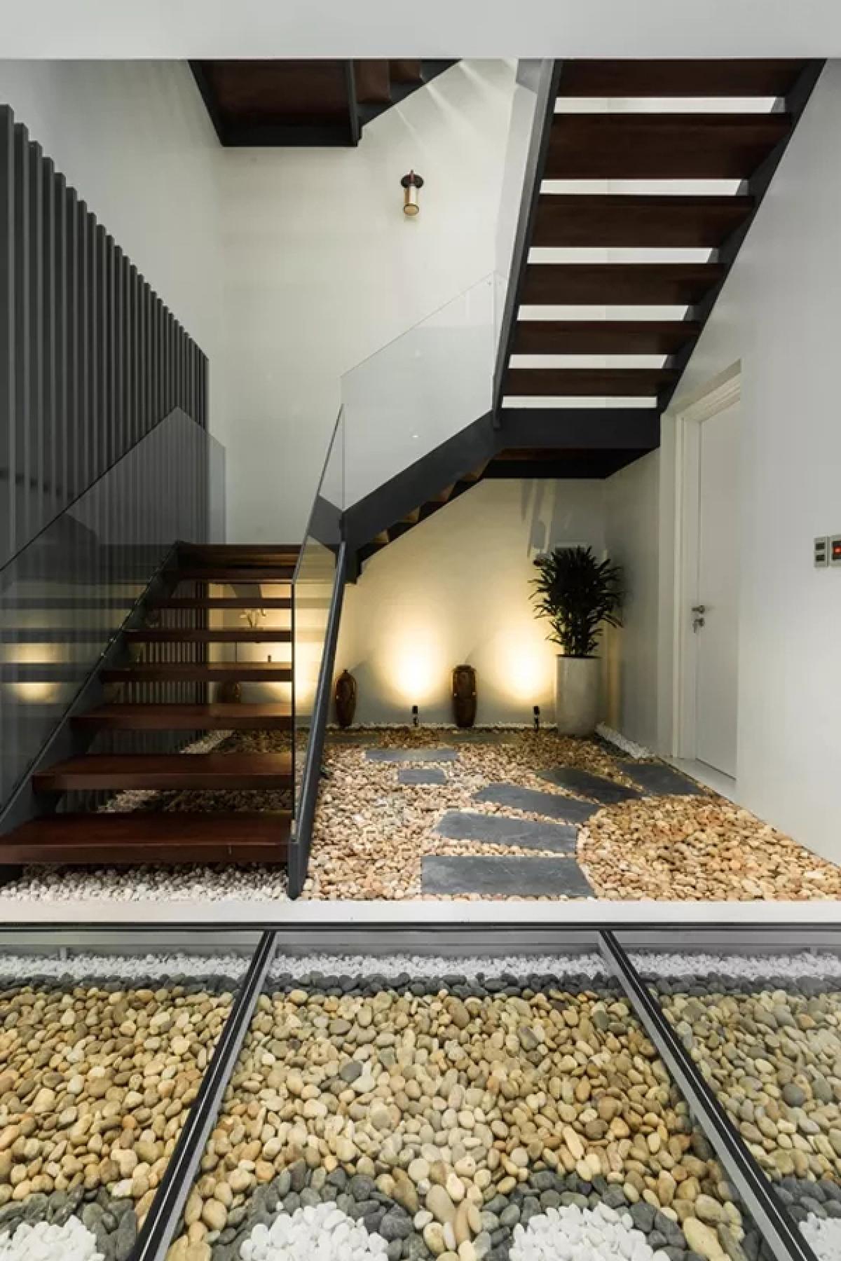 Hệ cầu thang sắt kết hợp bậc gỗ cùng lan can kính trong suốt, tạo nên cảm giác thoáng rộng. Bộ phận kiến trúc này ấn tượng như một tác phẩm điêu khắc hiện đại