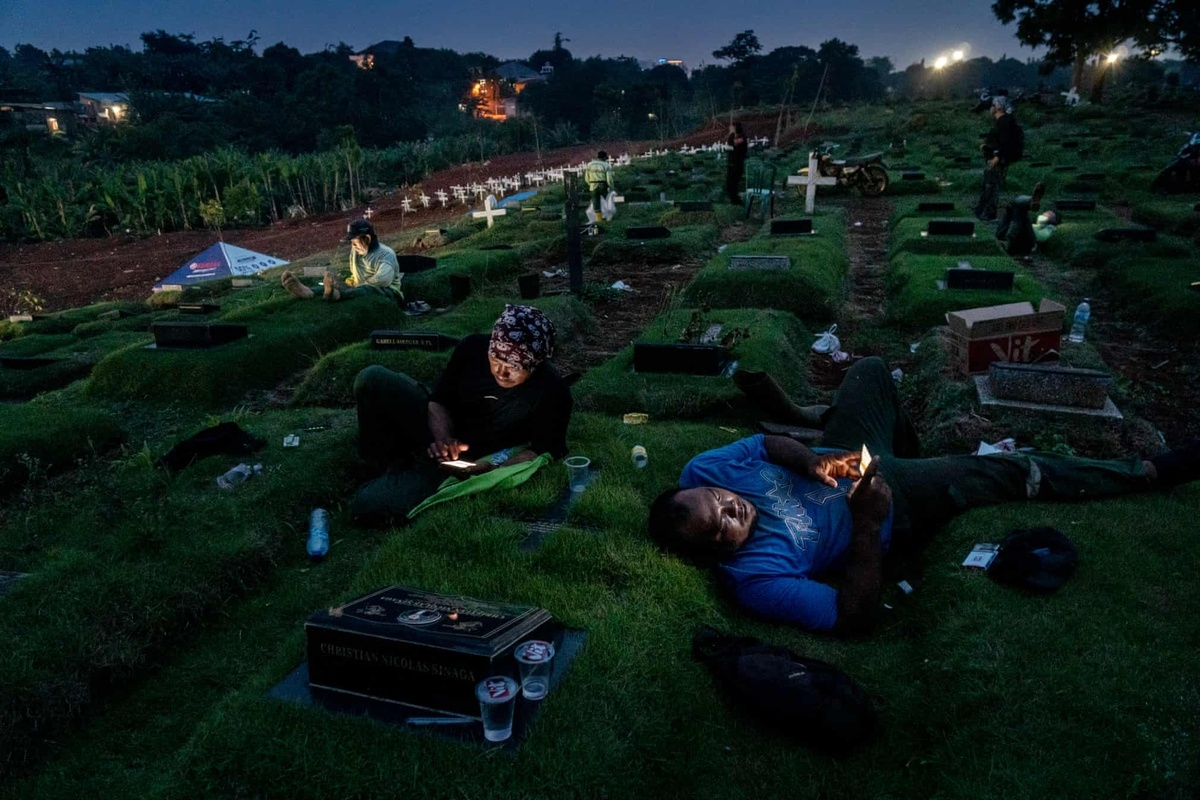 "A photo by Ares Jonekson Saragi makes the shortlist in the street photography category. The theme is ""Night in Pandemic Time"" and taken at the Pondok Ranggon Cemetery in Jakarta during the afternoon. Viewers can see the funeral officers having a break, watching videos on their smartphones, and chatting with their families."