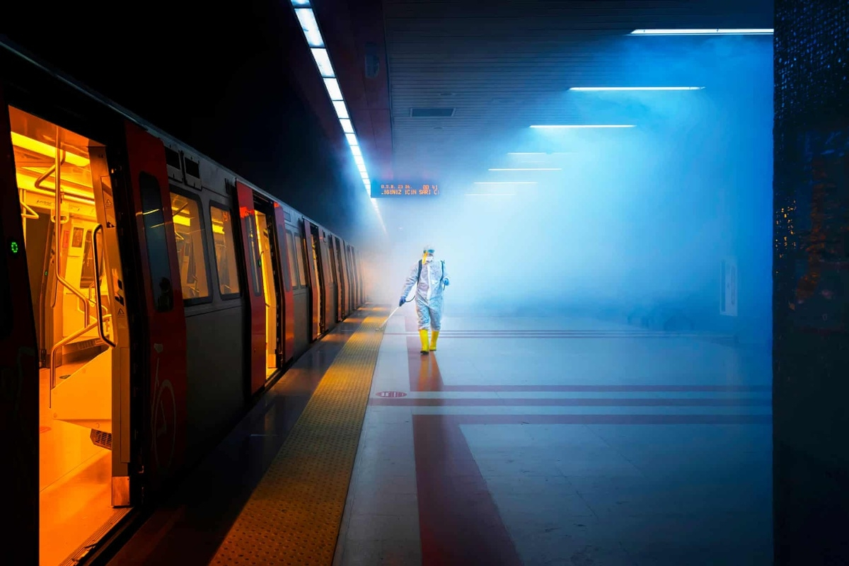 "Another image taken by F Dilek Uyar is named as the winner in the street photography category. ""Disinfection"" represents a cinematic image which documents an employee of the health affairs unit of Ankara municipality wearing protective gear as they walk along the train platform as they thoroughly spray it with disinfectant."