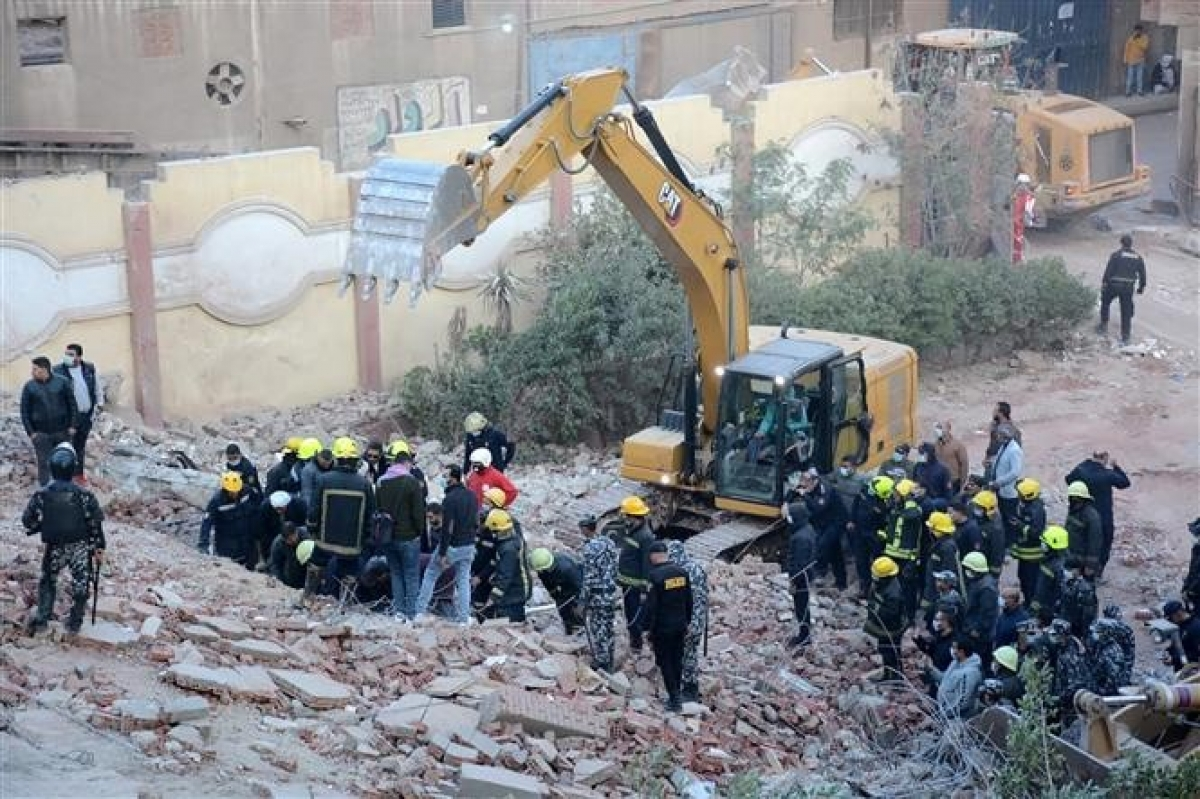 Lực lượng cứu hộ và tình nguyện viên tìm kiếm các nạn nhân tại hiện trường vụ sập toà nhà 10 tầng ở quận Gesr Giza, Cairo (Ai Cập) ngày 27/3/2021. (Ảnh: AFP)