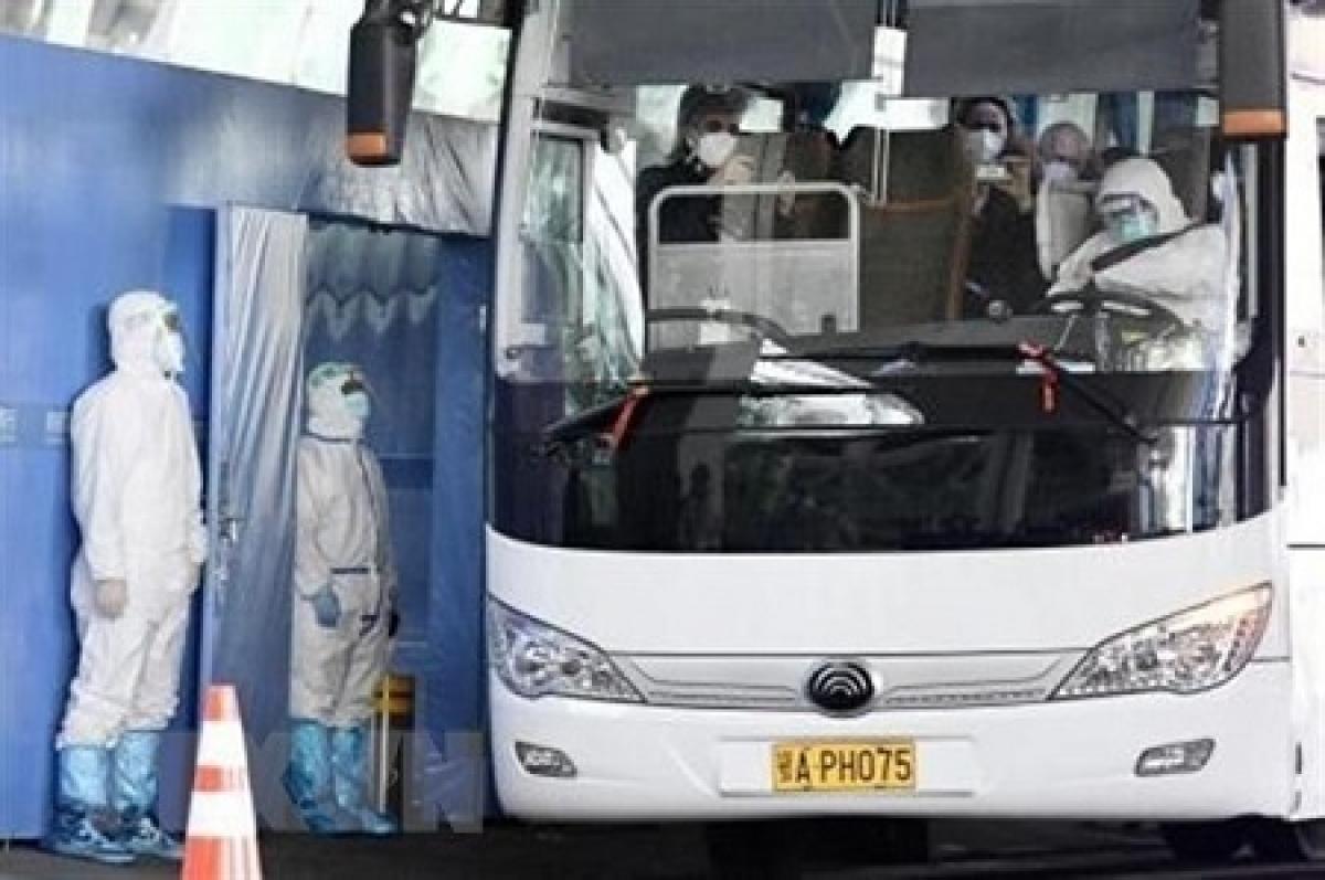 Xe buýt chở các chuyên gia của WHO sau khi họ tới Vũ Hán, Trung Quốc. Ảnh: Kyodo