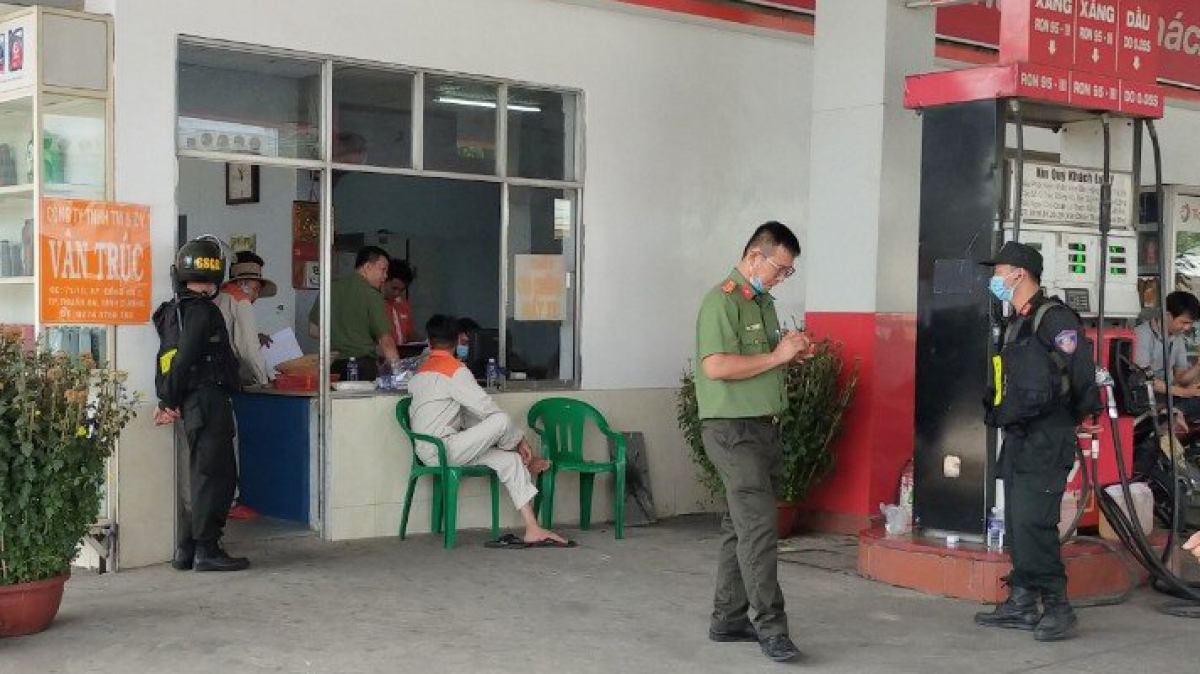 Bên trong cây xăng, lực lượng công an đang làm việc với nhân viên bán xăng.