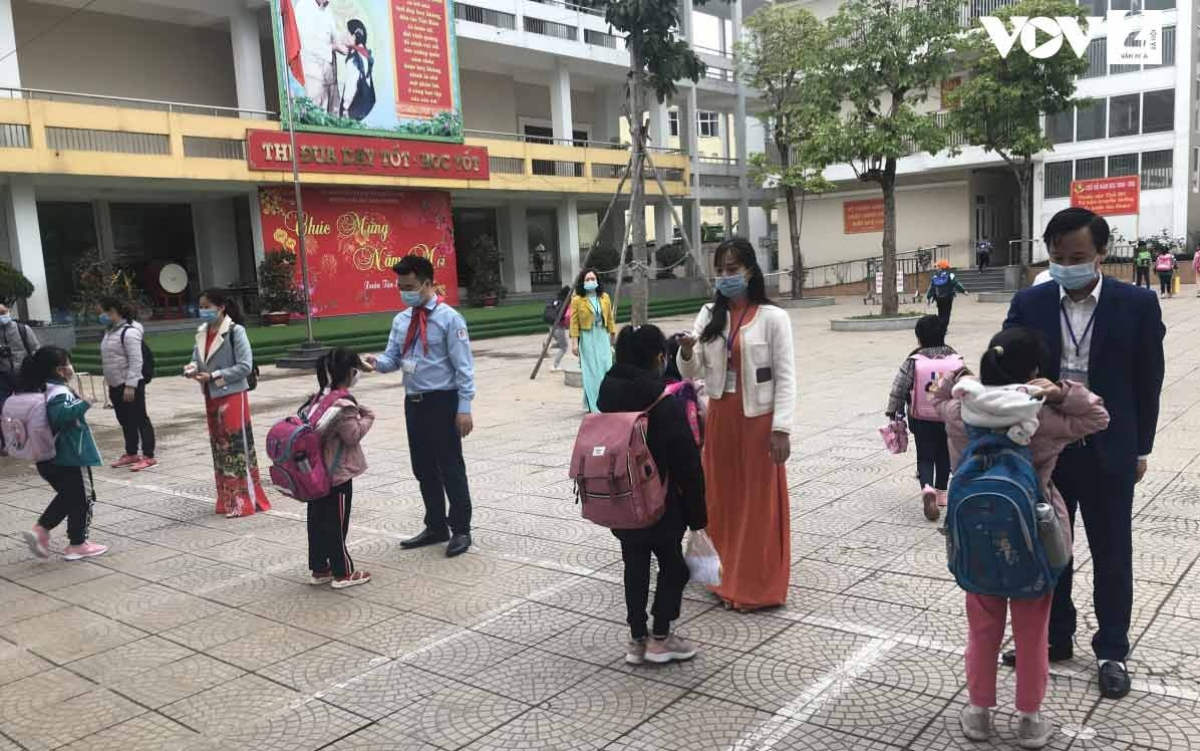 Học sinh Trường Tiểu học Xuân Phương được đo thân nhiệt trước khi vào lớp.