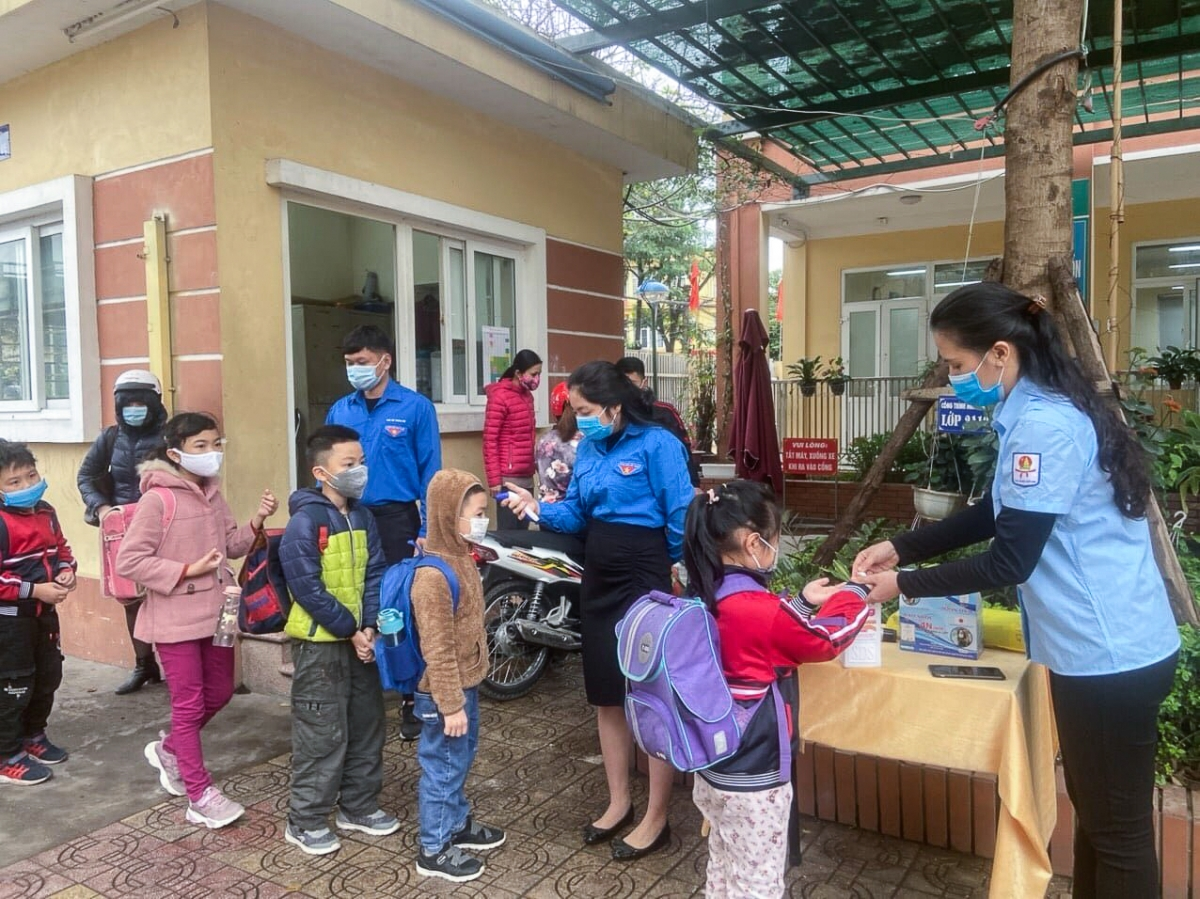 In Hanoi capital, the Youth Union assist a local primary school in measuring the body temperature of arrivals and guiding pupils on how to use hand sanitizer in the fight against the novel coronavirus (COVID-19).