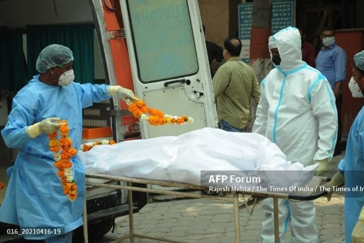 Các nhân viên y tế khiêng xác một bệnh nhân Covid-19 từ xe cấp cứu tại Nigambodh Ghat ở Delhi, Ấn Độ. Ảnh: AFP