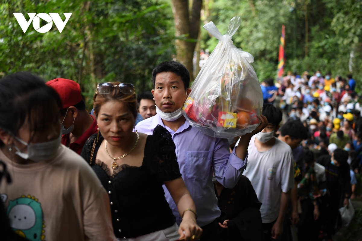 A family brings chicken, cakes, and various types of fruit as offerings to the Hung Kings.