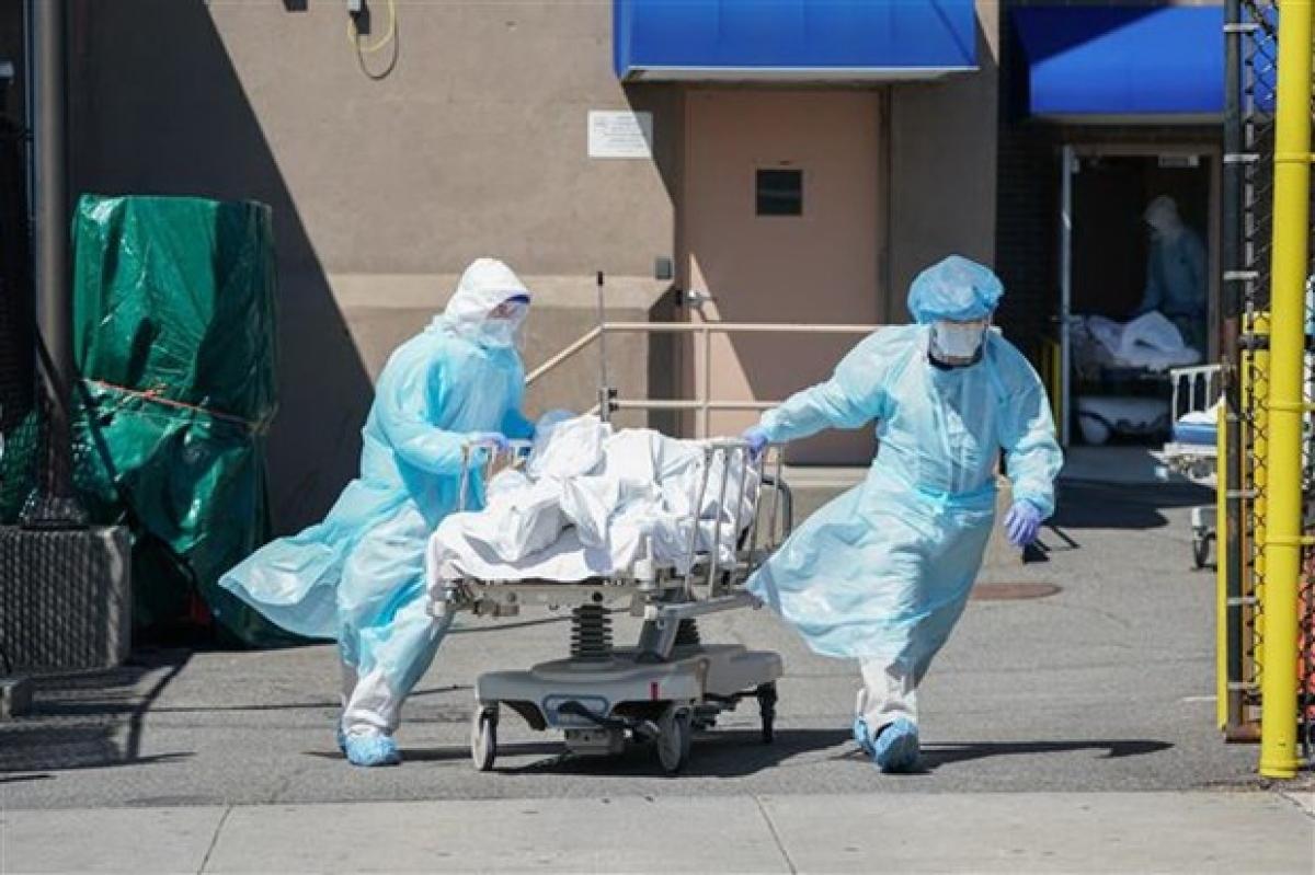 Nhân viên y tế chuyển thi thể bệnh nhân COVID-19 tới nhà xác dã chiến bên ngoài một bệnh viện ở New York, Mỹ. (Ảnh: AFP/TTXVN)