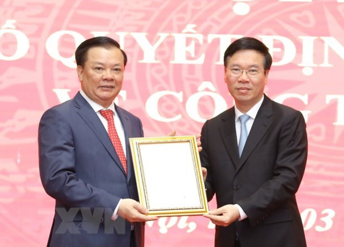 Permanent Member of the Party Central Committee's Secretariat Vo Van Thuong (R) hands over the Politburo's decision to new Secretary of the Party Committee of HanoiDinh Tien Dung(Photo: VNA)
