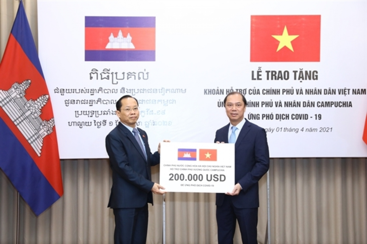 Presenting the Vietnamese gift to Cambodian Ambassador to Vietnam Chay Navuth, Deputy Foreign Minister Nguyen Quoc Dzung (R) hopes the gift will partly help Cambodia combat the COVID-19.