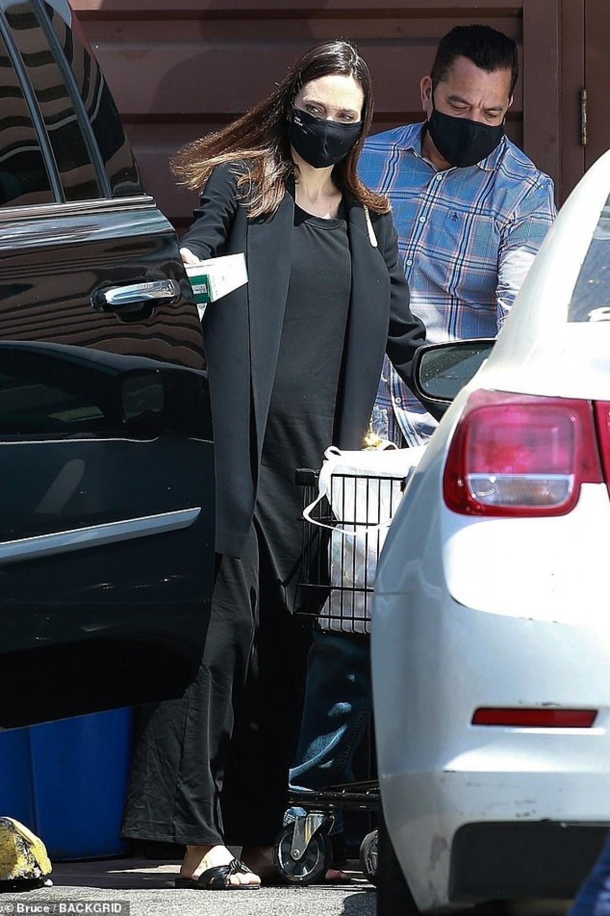 """Nữ diễn viên diện trang phục màu đen thanh lịch, buông xõa tóc và được vệ sĩ """"hộ tống"""" ra phố."""