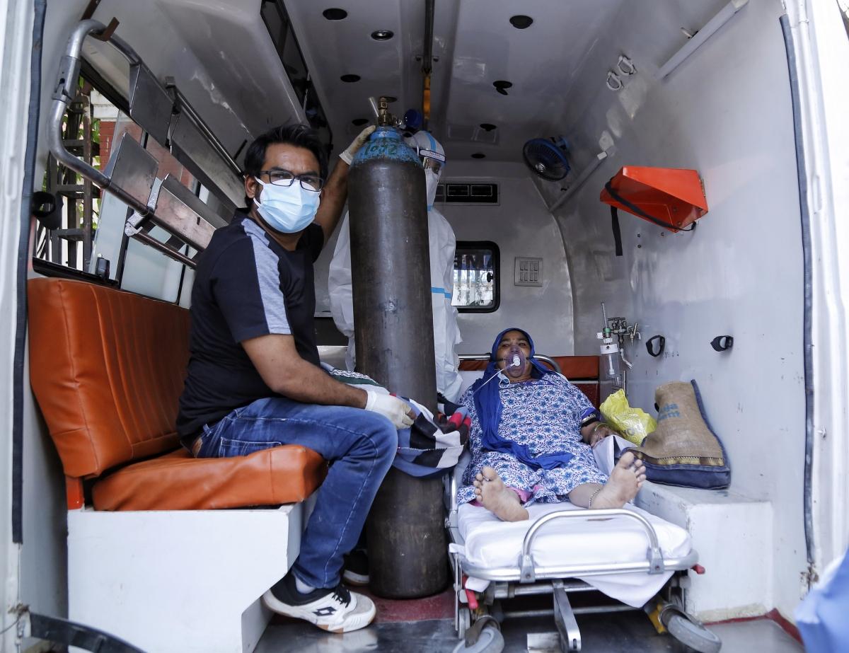 Một bệnh nhân Covid-19 phải thở oxy trong lúc chờ được xếp giường bệnh ở bệnh viện LNJP, thủ đô New Delhi. (Ảnh: ANI)