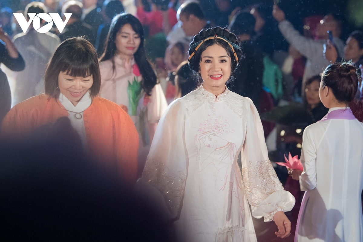 People's artist Thu Ha beams whilst wearing a white Ao Dai.