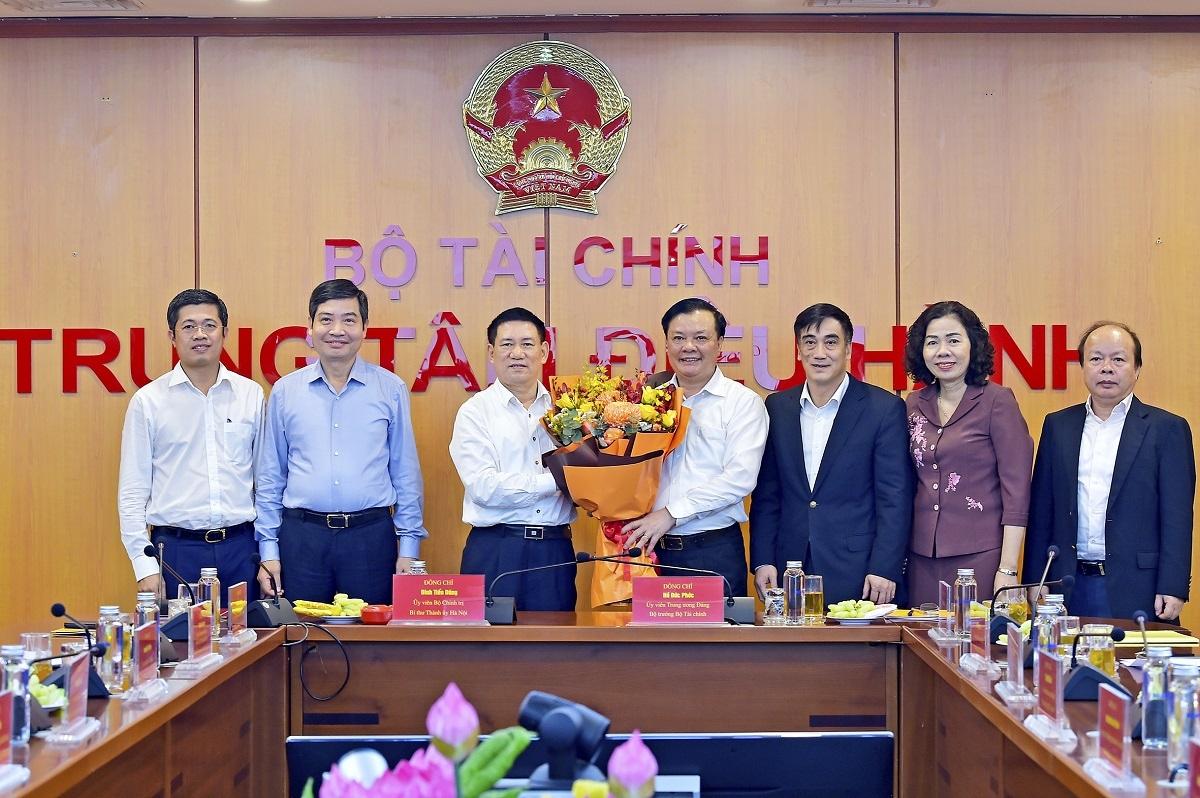 Các đồng chí Ủy viên Ban Cán sự đảng Bộ Tài chính tặng hoa Bộ trưởng Bộ Tài chính Hồ Đức Phớc và Bí thư Thành ủy Hà Nội Đinh Tiến Dũng.